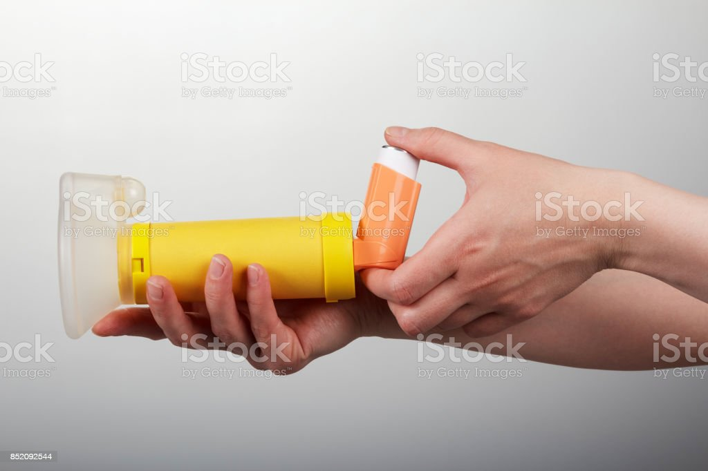 Inhaler spacer in the woman hands isolated on gray background stock photo