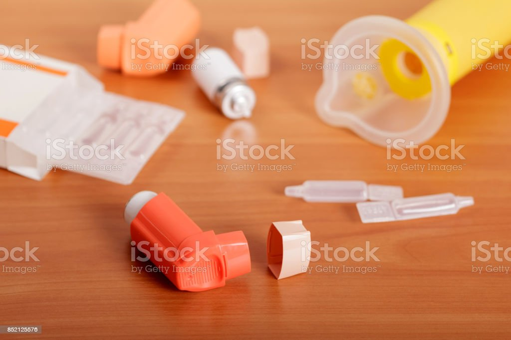 Inhalers aerosol, aerochamber box and medicine on the background of table. stock photo