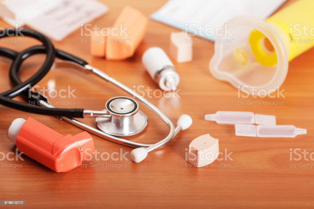 Inhalers aerosol, stethoscope, aerochamber, packaging and medicines on the background of table. stock photo
