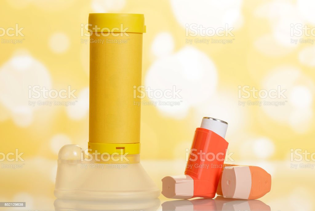 Inhalers and aerochamber on abstract yellow. stock photo
