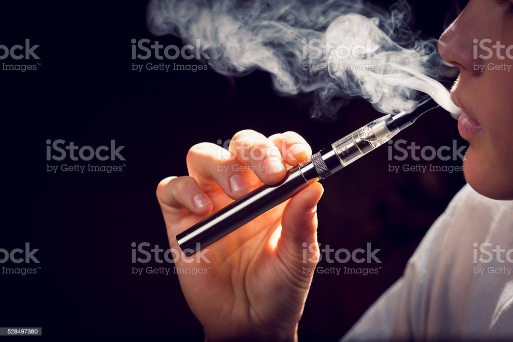 inhaling from an electronic cigarette. stock photo