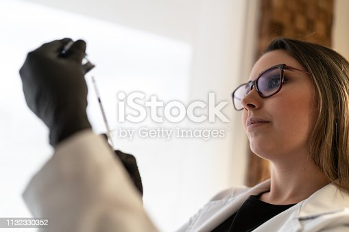 627196908 istock photo Injecting injection vaccine vaccination medicine flu woman doctor 1132330352
