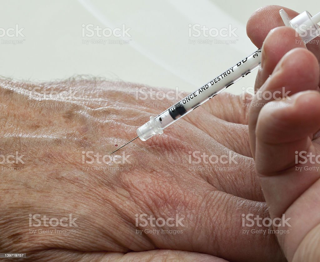 Injection into hand of senior male royalty-free stock photo