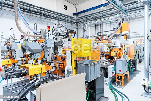 istock Injection moulding machines inside of plastic factory 639831158