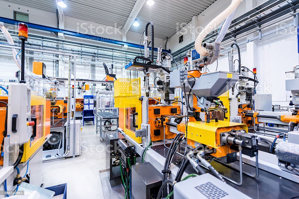 Injection moulding robots in factory - foto de acervo