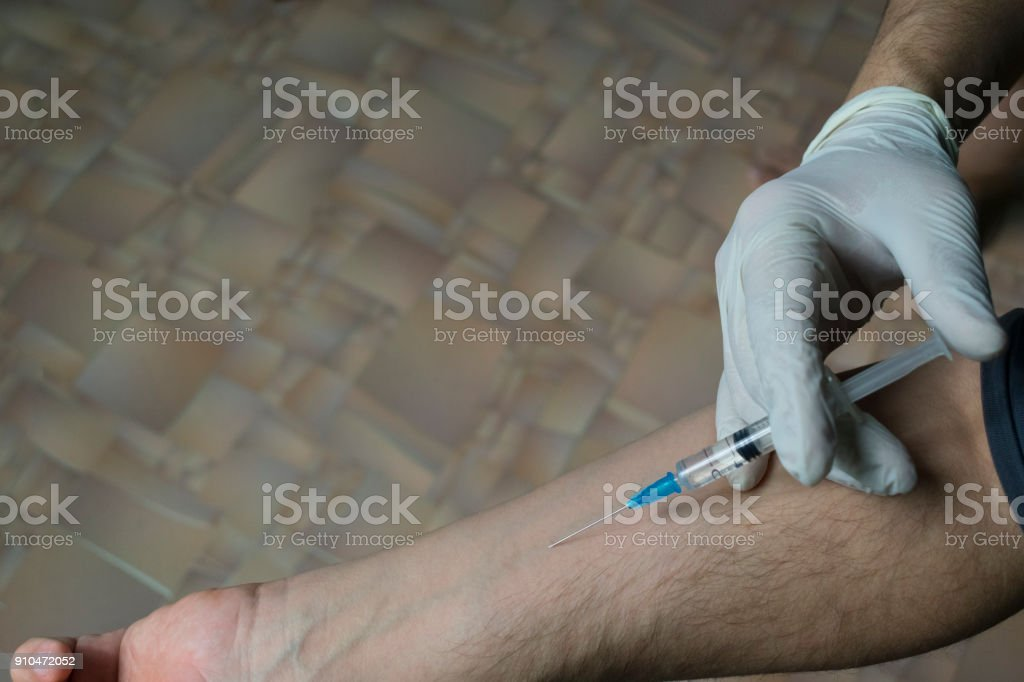 injection of a medical syringe into his hand, a medical glove stock photo