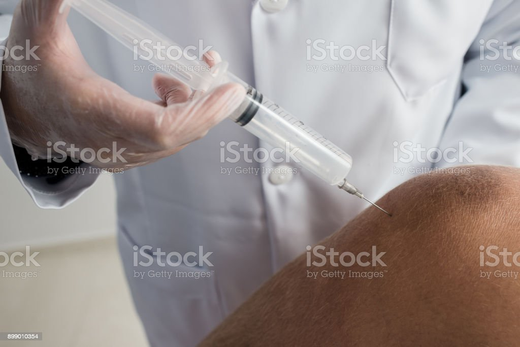 Injection of ozone in the knee, ozone therapy procedure stock photo