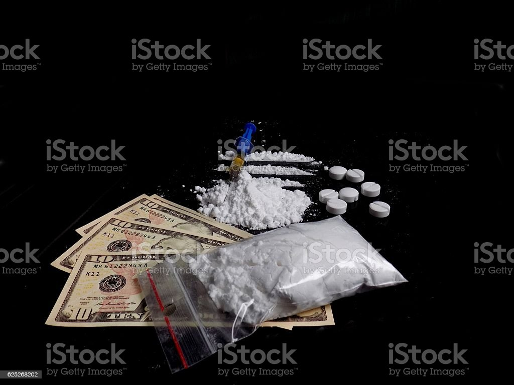 Injection syringe on cocaine, pills and dollar bills stock photo