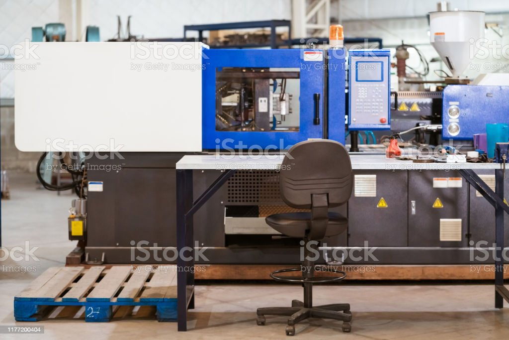 Injector machine in metal industry Office chair by injector machine in industry. Manufacturing machinery is in factory. Absence Stock Photo