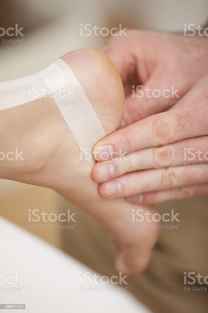 Injured ankle being bandaged by a doctor royalty-free stock photo