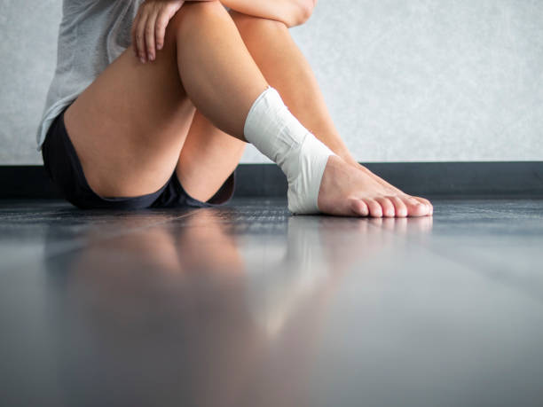 Injured athlete sitting on the sidelines due to ankle sprain stock photo