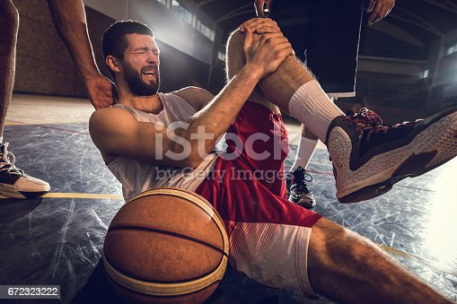 istock Injured basketball player holding his leg in pain on the court. 672323222