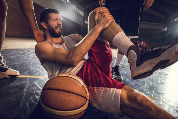 Injured basketball player holding his leg in pain on the court. stock photo