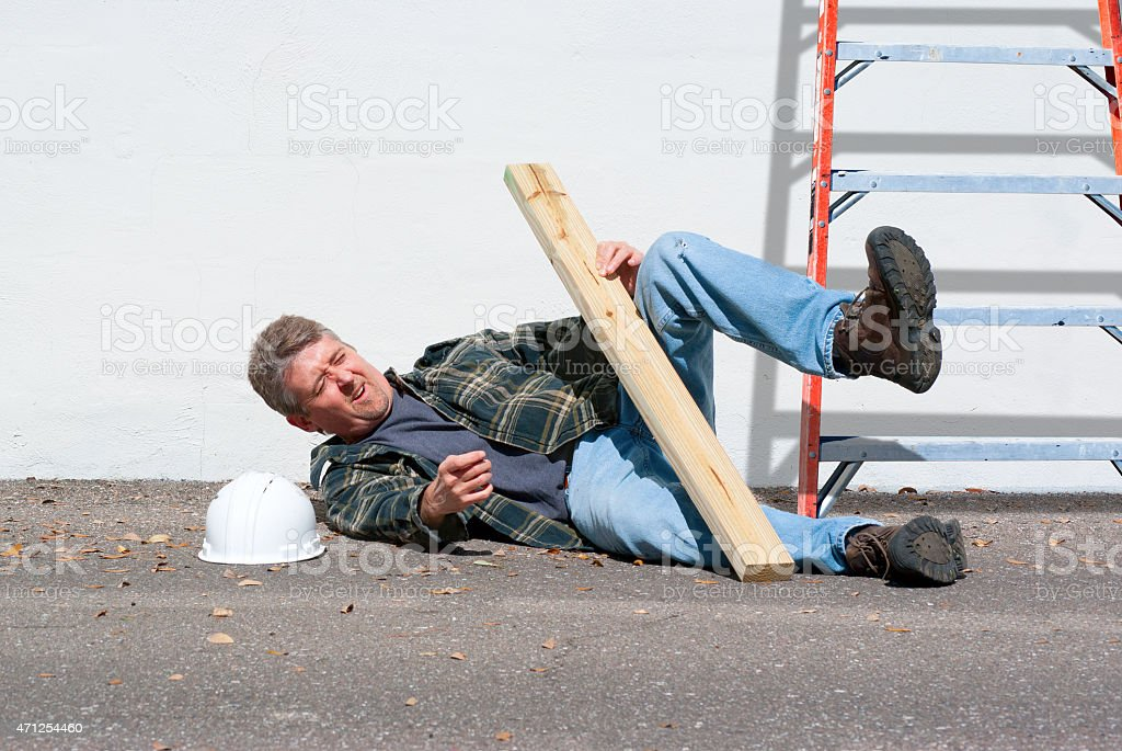 Injured construction worker fallen off ladder stock photo