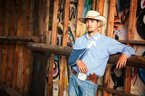 Portrait of a young cowboy resting in barn. One of his arms is in a sling.