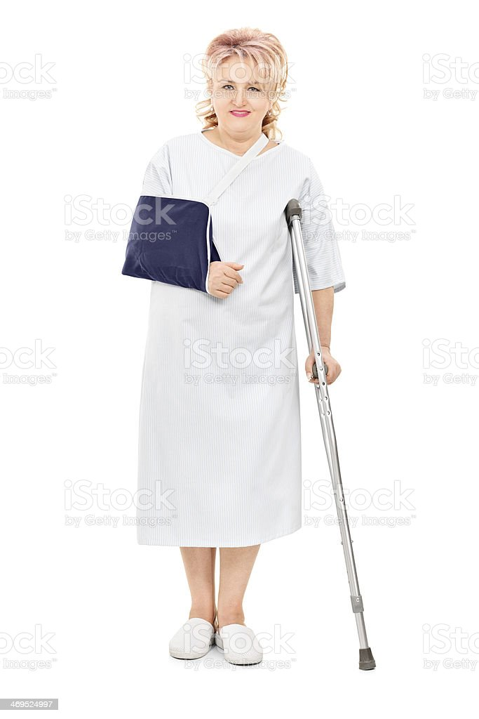 Injured female patient standing with crutch royalty-free stock photo
