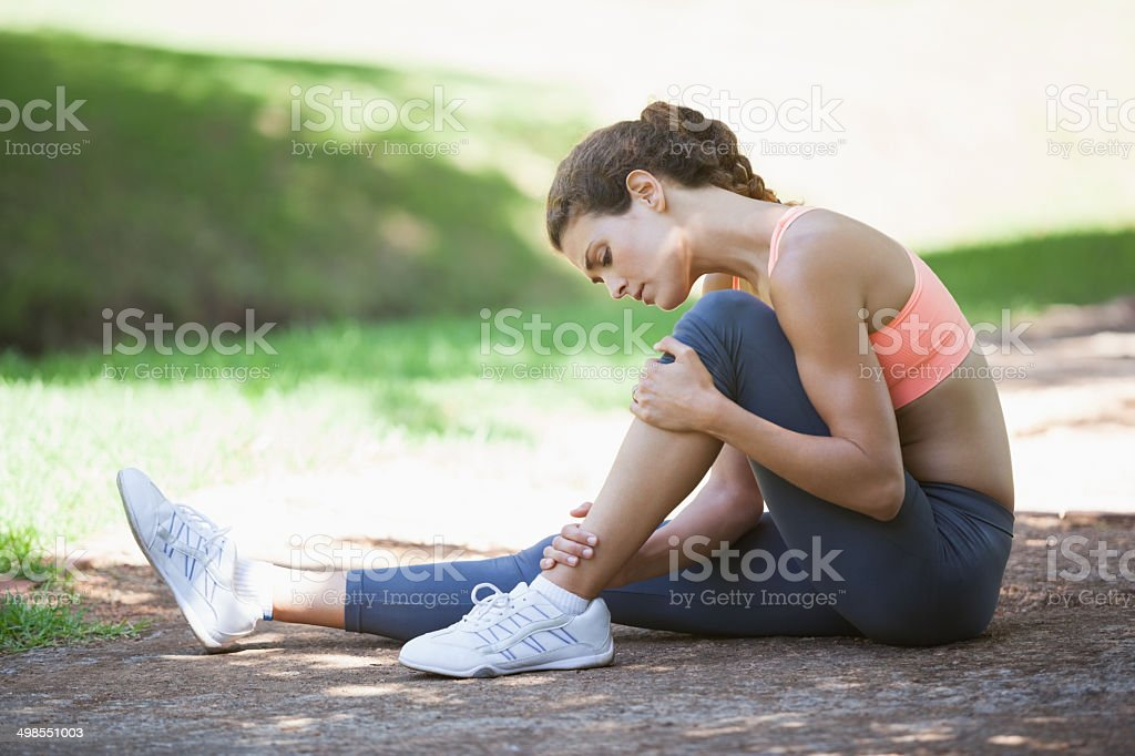 Injured fit woman touching her leg on the path stock photo