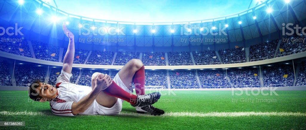 Injured football player on stadium field stock photo