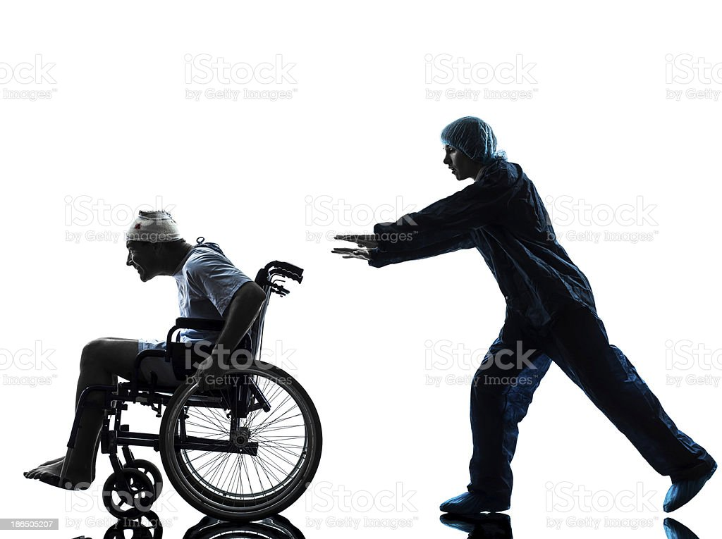 injured funny man in wheelchair escaping away of nurse silhouette royalty-free stock photo