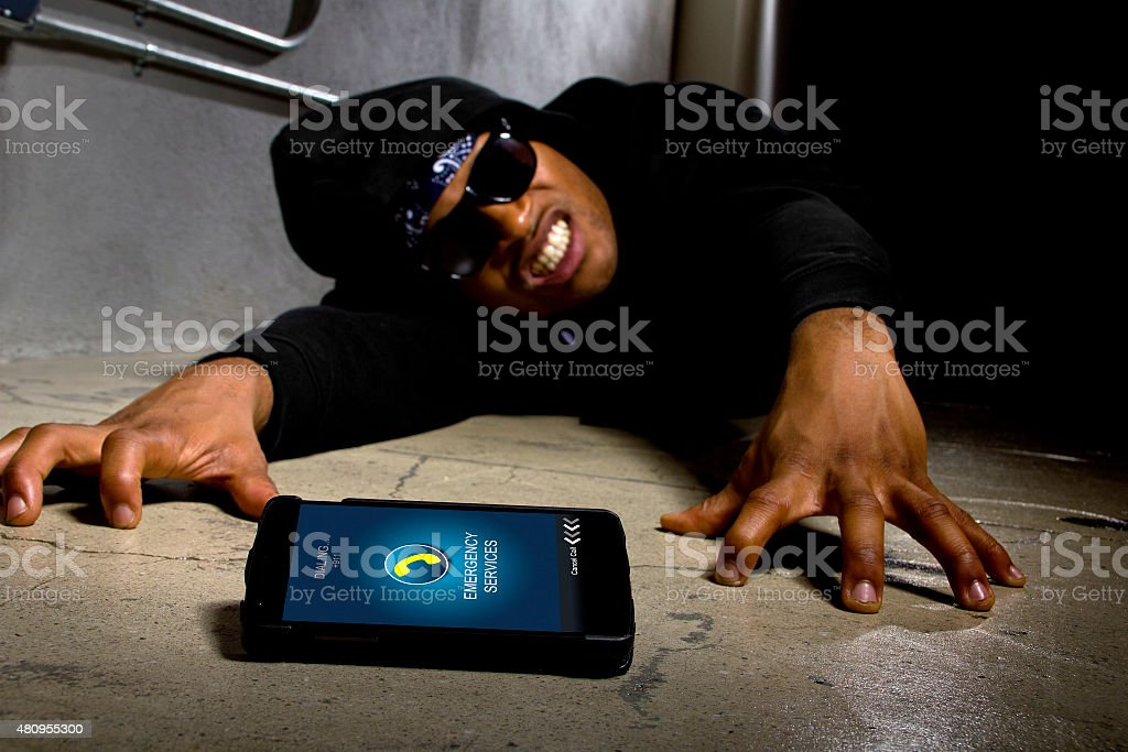Injured Gangster Calling 911 for Help stock photo