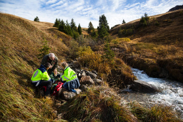 Injured girl tended by Swiss mountain rescue while concerned grandfather watches on stock photo