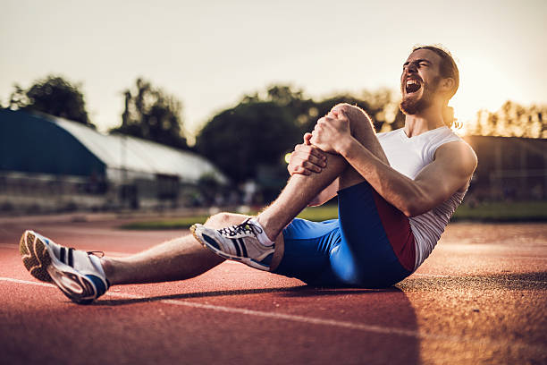 injured male athlete screaming in pain at sunset. - human knee stock photos and pictures