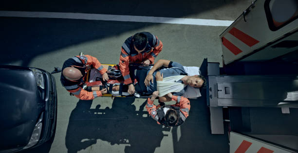 injured male cyclist being loaded into ambulance on stretcher - paramedic stock pictures, royalty-free photos & images