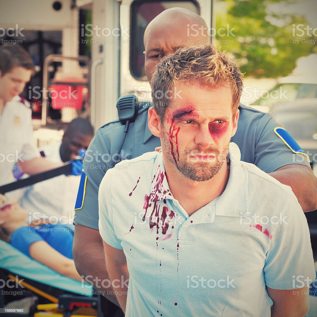 Injured man being arrested by police officer stock photo