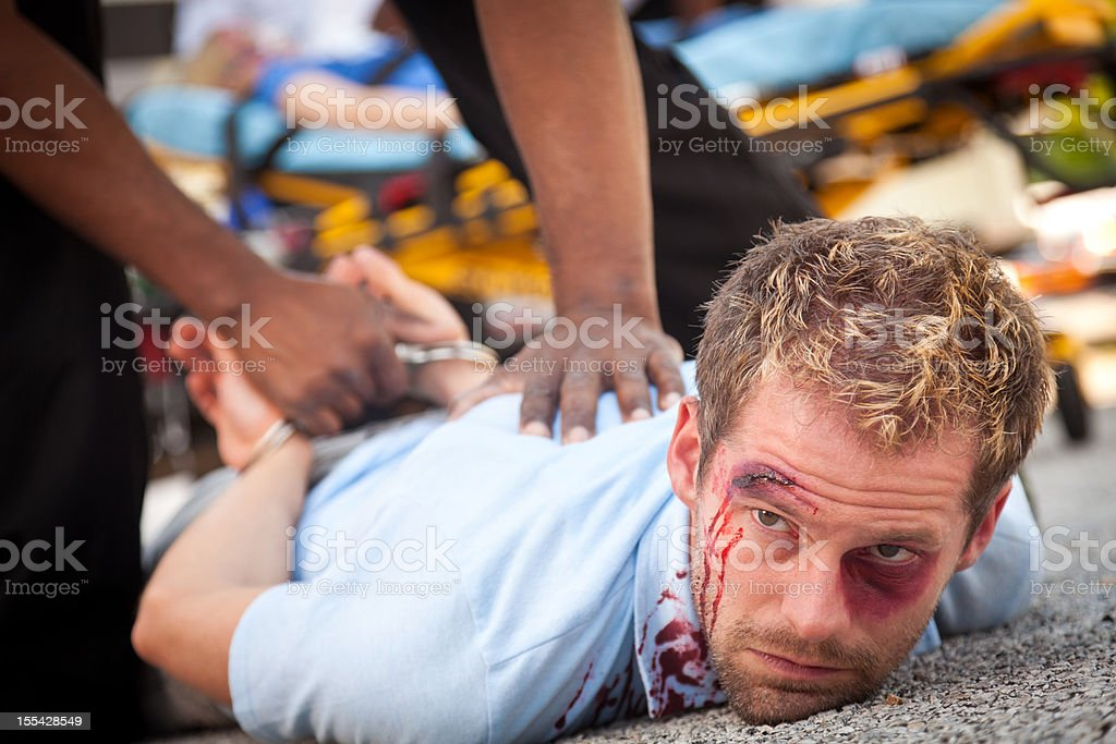 Injured man being forced down and arrested stock photo
