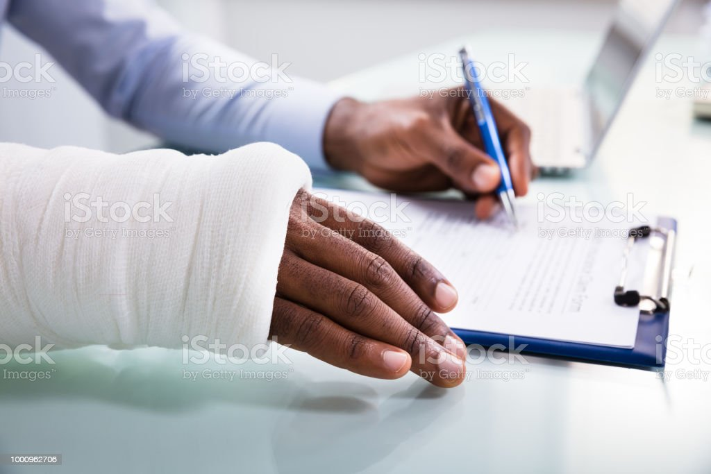 Injured Man Filling Insurance Claim Form stock photo