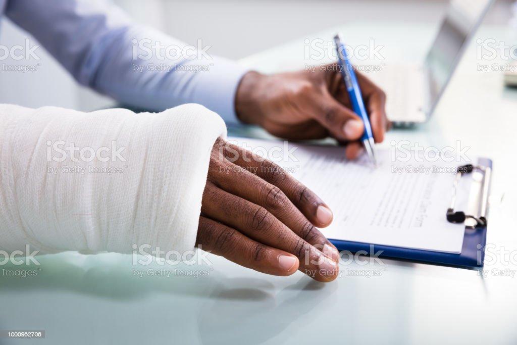 Herido hombre rellenando el formulario de reclamo de seguro - foto de stock