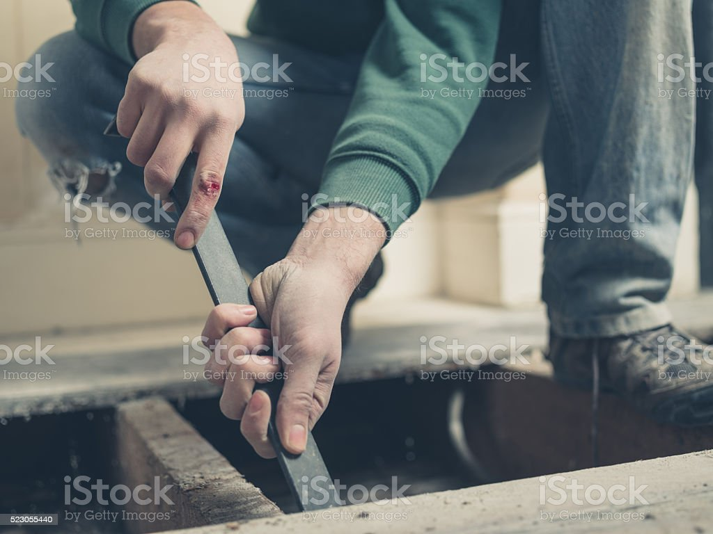 Injured man using a crowbar on floor boards stock photo
