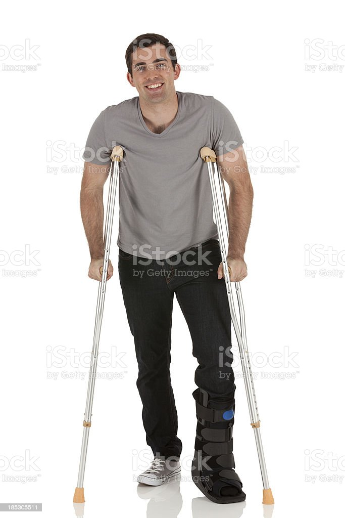 Injured man walkiing with the help of crutches royalty-free stock photo