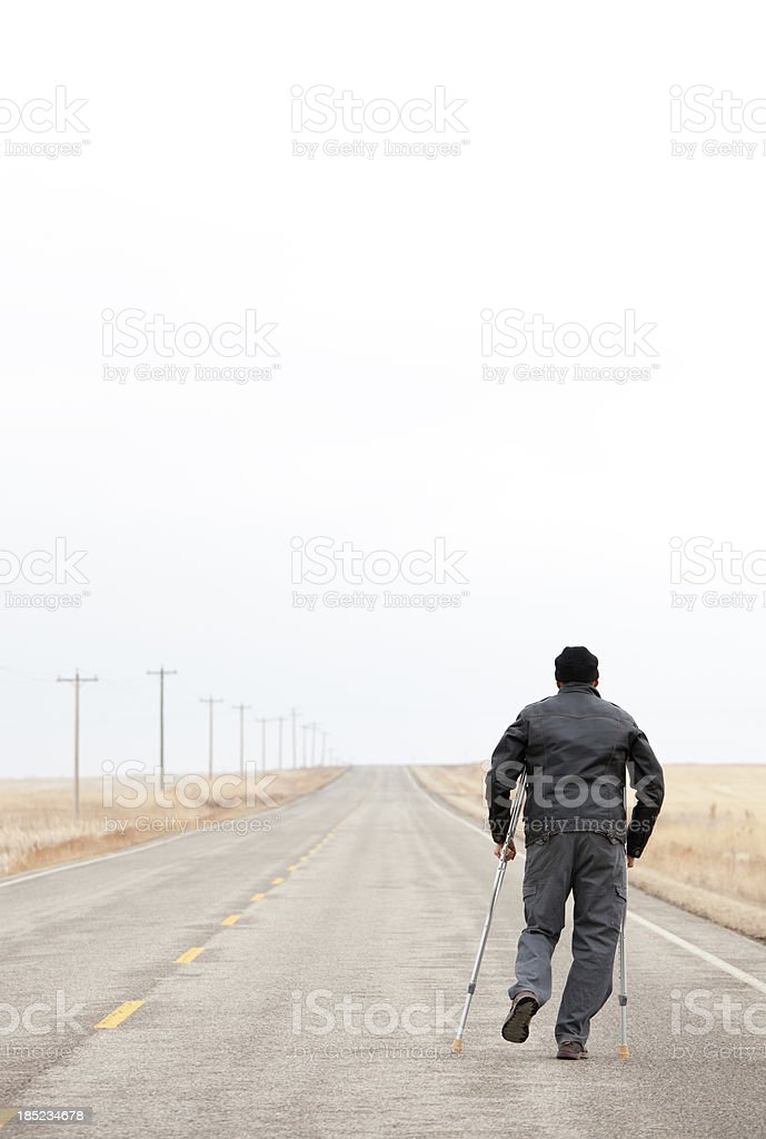 Injured Man Walking Down A Desolate Highway With Crutches stock photo