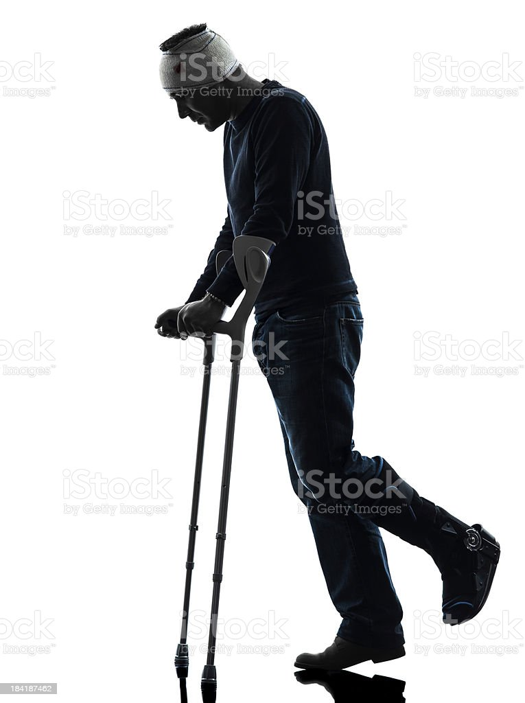 injured man walking sad with crutches silhouette royalty-free stock photo