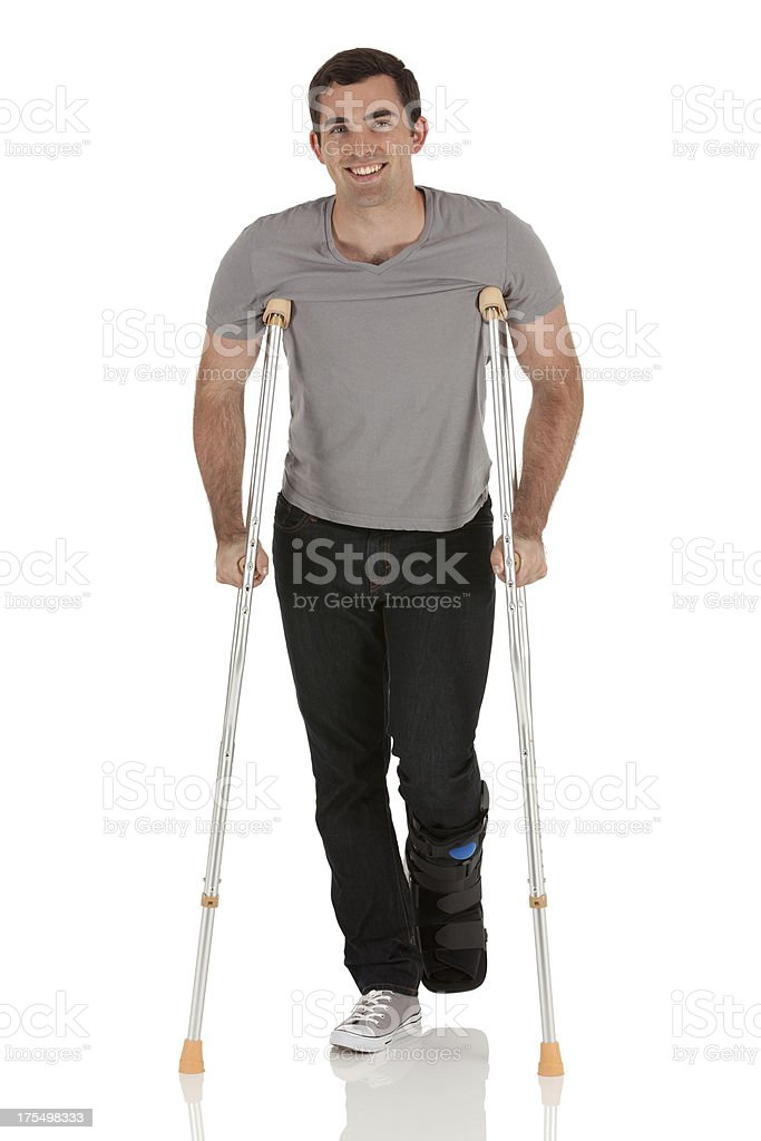 Injured man walking with the help of crutches stock photo