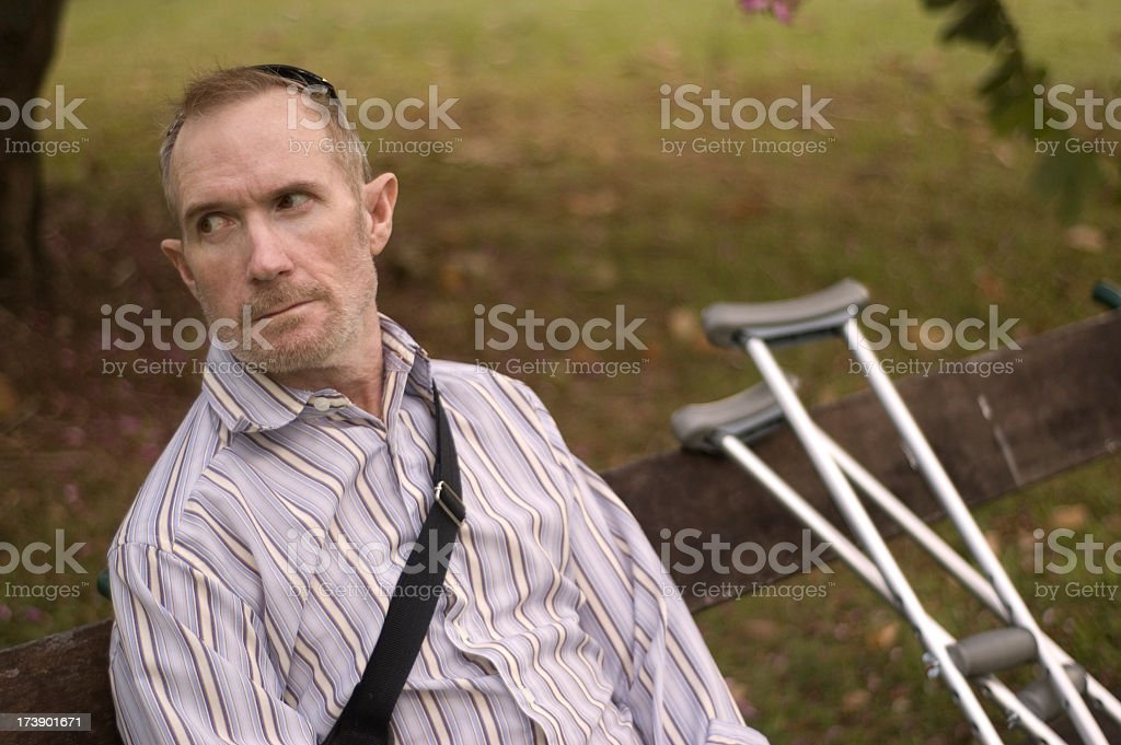 Injured man with crutches stock photo