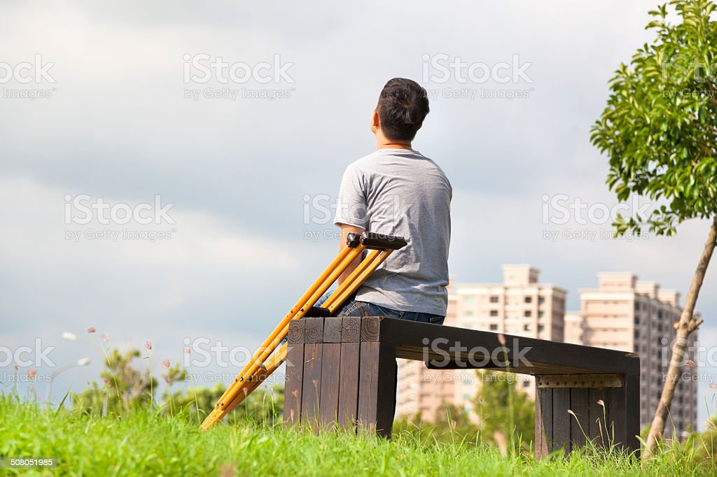 Injured Man with Crutches sitting on a bench stock photo