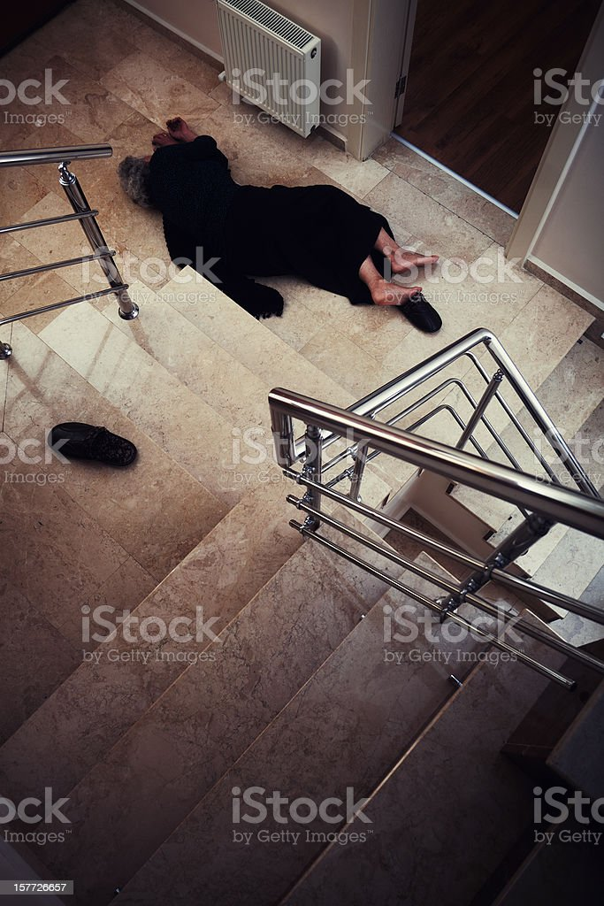 Injured person lying at the bottom of a winding stairwell stock photo