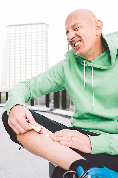 Injured Runner Applying Some Ointment On His Leg stock photo