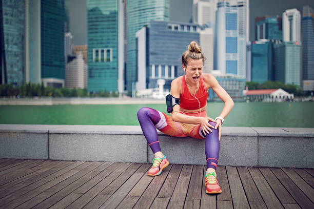 Injured runner girl is sitting and holding her knee stock photo