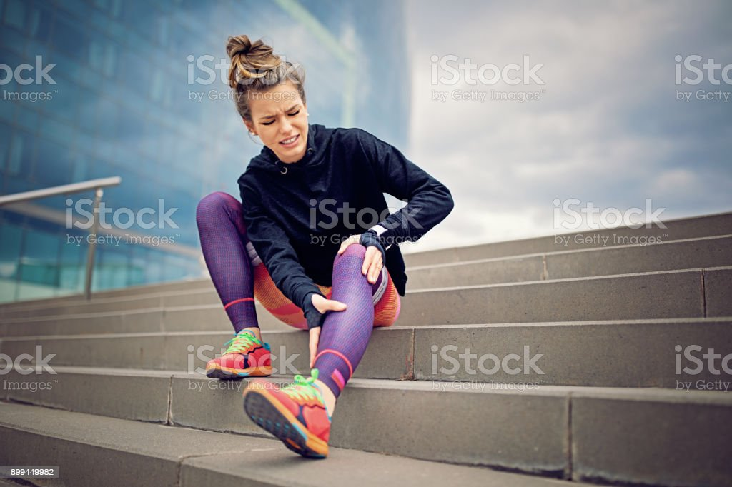 Injured runner girl is sitting on the city stairs stock photo