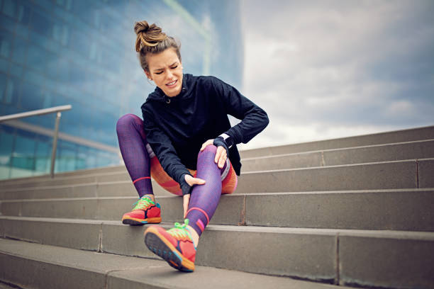 injured runner girl is sitting on the city stairs - pain stock photos and pictures
