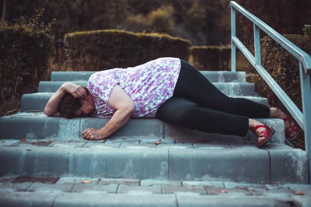 Injured senior woman fallen on the stairs outdoors stock photo