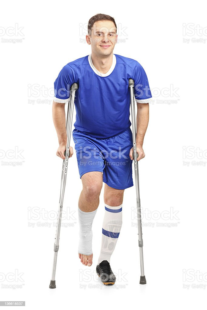 Injured soccer football player on crutches stock photo
