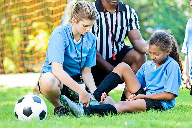 injured soccer player getting her ankle checked by her coach - kinder die schnell arbeiten stock-fotos und bilder