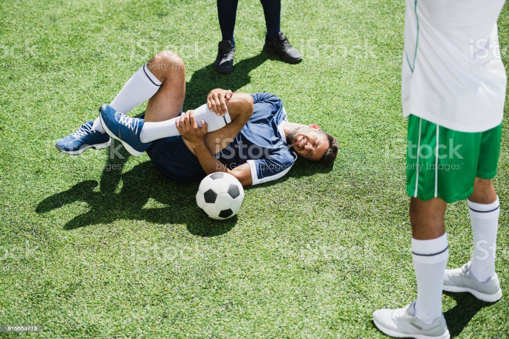 injured soccer player lying on football field during match stock photo