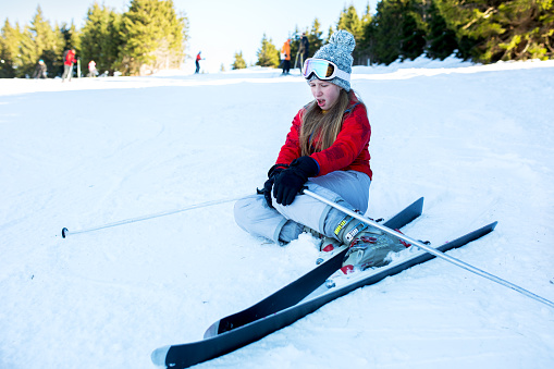 Injured teenage girl on snow holding her leg in pain.