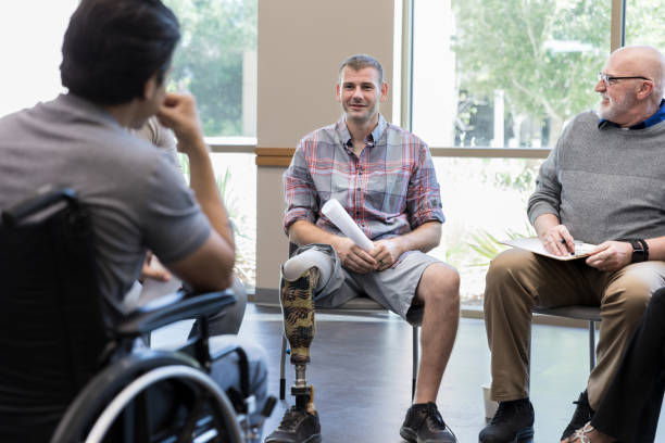 Injured veterans talk with each other during support group meeting stock photo