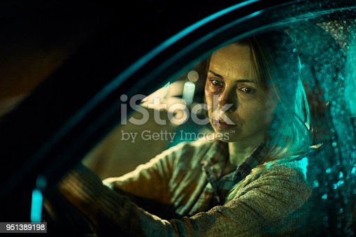 Close up of a injured and scared woman driving a car